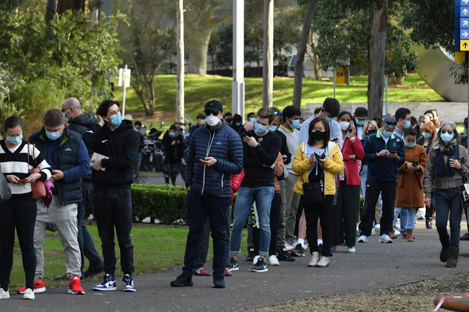 People are seen queued to receive their vaccination at the NSW Vaccine Centre at Homebush Olympic Park in Sydney, Monday, July 12, 2020. NSW recorded 112 new locally acquired cases of COVID-19 in the 24 hours to 8pm last night. (AAP Image/Mick Tsikas) NO ARCHIVING