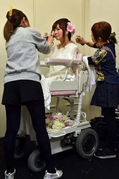 Make-up artists work on disabled model Ami Sano (C) as she sits in her electric wheelchair during the Tokyo Fashion Week's 2015-16 autumn/winter collection on March 18, 2015 (AFP Photo/Yoshikazu Tsuno)