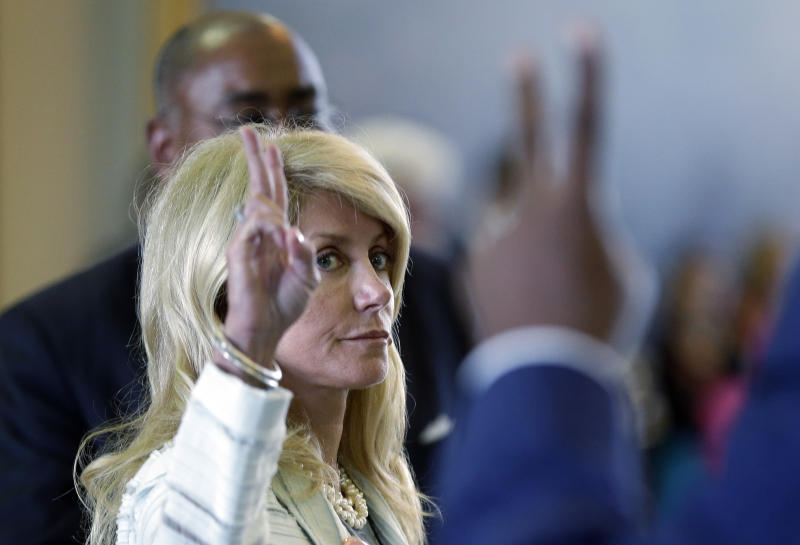 Sen. Wendy Davis, D-Fort Worth, left, votes against a motion to call for a rules violation during her filibusters of an abortion bill, Tuesday, June 25, 2013, in Austin, Texas. Davis was given a second warning for breaking filibuster rules by receiving help from Sen. Rodney Ellis, D-Houston, with a back brace. (AP Photo/Eric Gay)