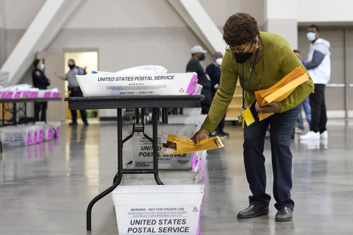 A election official works around ballots during a Milwaukee hand recount of presidential votes at the Wisconsin Center, Friday, Nov. 20, 2020, in Milwaukee. The recount of the presidential election in Wisconsin's two most heavily Democratic counties began Friday with President Donald Trump's campaign seeking to discard tens of thousands of absentee ballots that it alleged should not have been counted. (AP Photo/Nam Y. Huh)