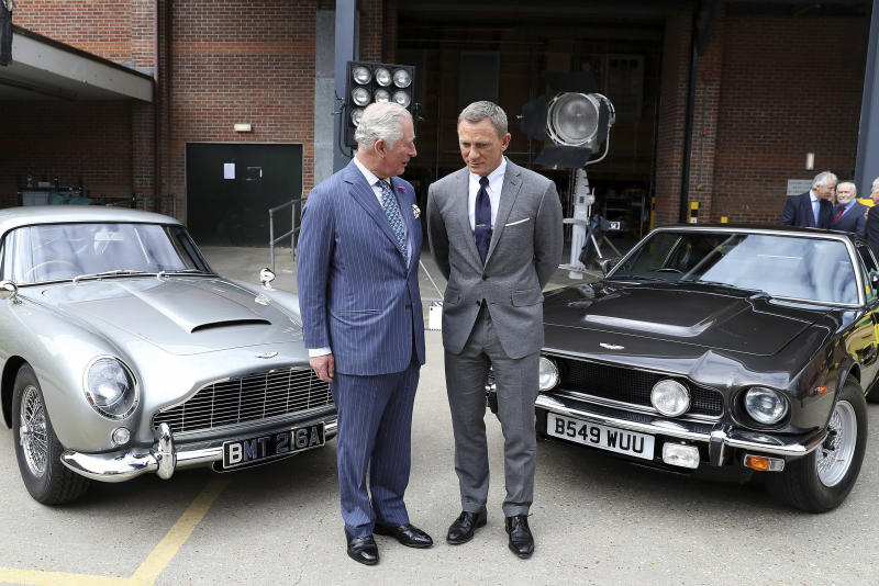Britain's Prince Charles talks with actor Daniel Craig, right, during a visit to the set of the 25th James Bond film at Pinewood Studios in Iver Heath, southern England, Thursday June 20, 2019. (Chris Jackson/PA via AP)