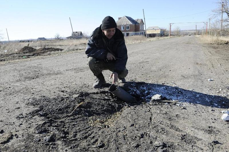 A Ukrainian soldier examines a crater after a night shelling in the eastern village of Pavlopil, Donetsk region, on October 28, 2014 (AFP Photo/Alexander Khudoteply)