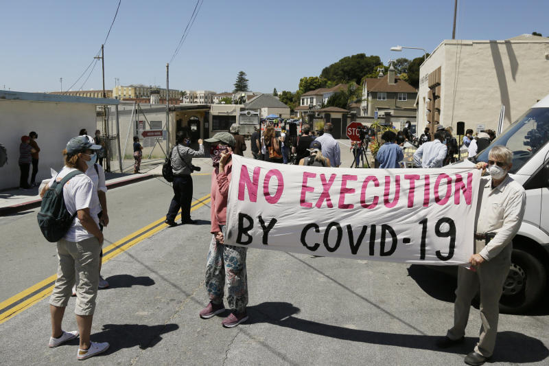 Two men hold up a banner before the start of a news conference outside San Quentin State Prison in San Quentin, Calif., on July 9, 2020. (Eric Risberg / AP)