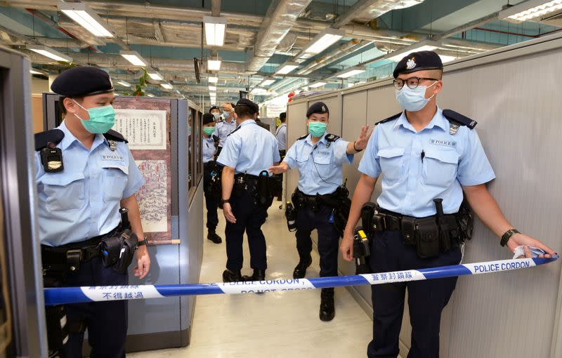 Hong Kong police officers set up police cordon as they search Apple Daily office in Hong Kong