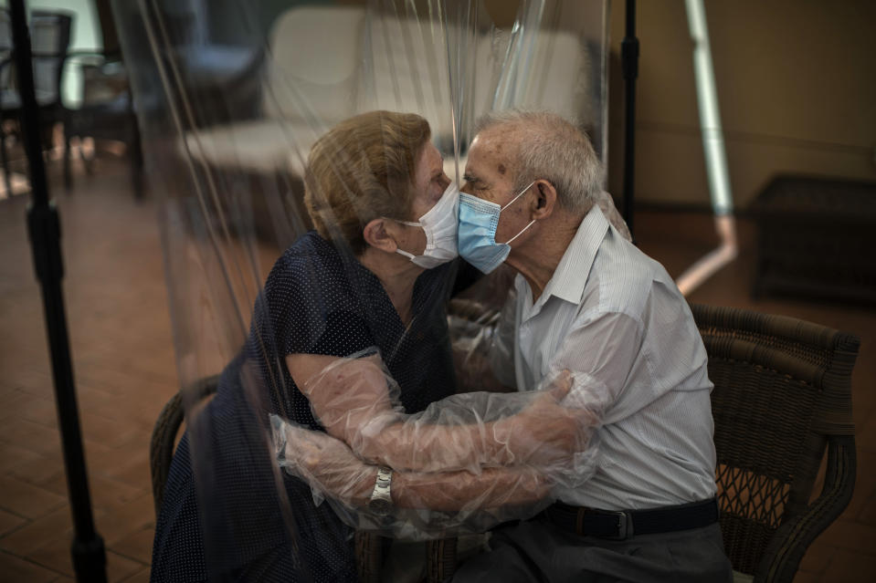 """Agustina Canamero, 81, and Pascual Pérez, 84, hug and kiss through a plastic film screen to avoid contracting the new coronavirus at a nursing home in Barcelona, Spain, June 22, 2020. Associated Press photographer Emilio Morenatti says this of the image: """"I couldn't help feeling emotional myself while I was shooting, and I realized that such an eternal moment symbolized something more than a simple meeting. The plastic kept the virus but not the love away."""" (AP Photo/Emilio Morenatti)"""