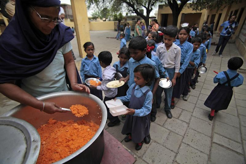 Children stand in a queue to receive a free mid-day meal made of sweetened rice at a government school on the outskirts of Jammu, India, Tuesday, May 6, 2014. The Mid-Day Meal is a massive school feeding program reaching out to millions of children in primary schools across India, mainly to enhance school enrollment and attendance and improve nutritional levels among children. (AP Photo/Channi Anand)