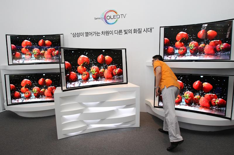 A journalist takes a close look at a Samsung Electronics Co.'s 55-inch curved OLED TV during a press conference at its headquarters in Seoul, South Korea, Thursday, June 27, 2013. After delays, Samsung rolled out Thursday a curved TV that uses an advanced display called OLED. The 55-inch TV will sell for 15 million won ($13,000) in South Korea, more than five times the cost of LCD televisions of the same size. (AP Photo/Ahn Young-joon)