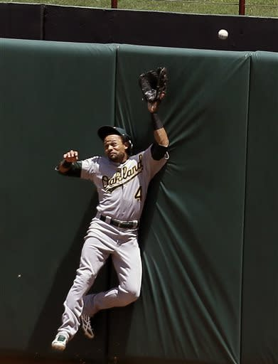Oakland Athletics' Coco Crisp (4) slams against the centerfield wall while chasing a solo home run by Texas Rangers' Geovany Soto in the fifth inning of a baseball game on Thursday, June 20, 2013, in Arlington, Texas. (AP Photo/Tony Gutierrez)