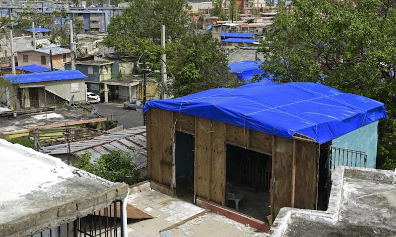 Fema tarps cover homes in San Juan. Fema said it has provided 65,000 tarps but many are still without a roof over their head.