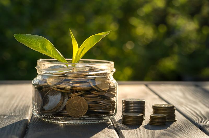 Leaves growing out of a small jar of coins.
