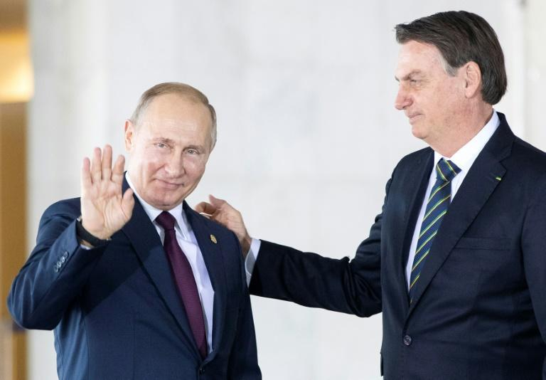 Russia's President Vladimir Putin (L) shakes hands with Brazil's President Jair Bolsonaro (R) before the 11th BRICS Summit at the Itamaraty palace on November 14, 2019 in Brasilia, Brazil