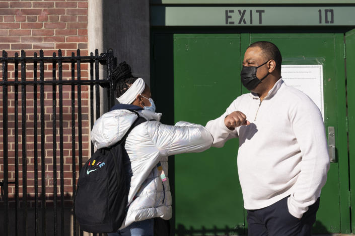 FILE - In this Feb. 25, 2021 file photo, Linsey Johnson, right, a dean at Meyer Levin Middle School, greets a student in New York. With COVID-19 cases soaring nationwide, school districts across the U.S. are yet again confronting the realities of a polarized country and the lingering pandemic as they navigate mask requirements, vaccine rules and social distancing requirements for the fast-approaching new school year. (AP Photo/Mark Lennihan, File)