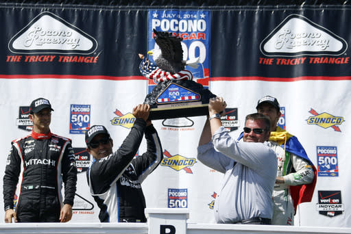Juan Pablo Montoya, second from left, of Colombia, hoists the trophy in victory lane with Pocono Raceway president Brandon Igdalsky, second from right, after Montoya won the Pocono IndyCar 500 auto race, Sunday, July 6, 2014, in Long Pond, Pa. Looking on is second place-finisher Helio Castroneves, left, of Brazil, and third place-finisher Carlos Munoz, right, of Colombia. (AP Photo/Matt Slocum)