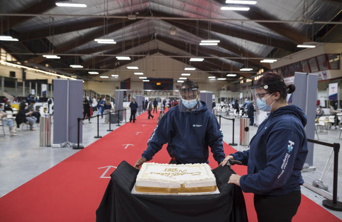 A cake is rolled out to celebrate the nursing students for the class of 2021, so they can gather around the cake during a mini celebration at the Downsview Arena vaccination site, in Toronto, Friday, April 16, 2021. (Tijana Martin/The Canadian Press via AP)
