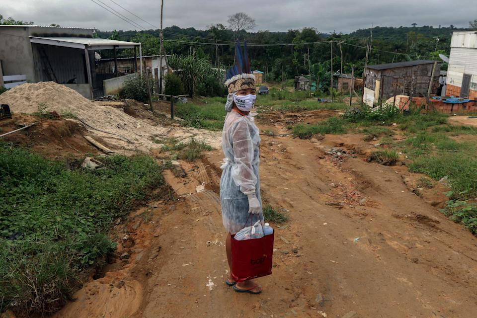 "Witoto indigenous nursing assistant Vanda Ortega, 32, poses for a picture before starting her round of healthcare visits in the Parque das Tribos, an indigenous community in the suburbs of Manaus, Amazonas State, Brazil, on May 3, 2020 during the COVID-19 novel coronavirus pandemic. - Ortega goes from house to house equipped with gloves, a protective gown and a mask in which one can read: ""The Life of Indigenous People Matters"", a message inspired by the slogan ""Black Lives Matter"" of black militants in the United States. (Photo by Ricardo OLIVEIRA / AFP) (Photo by RICARDO OLIVEIRA/AFP via Getty Images)"