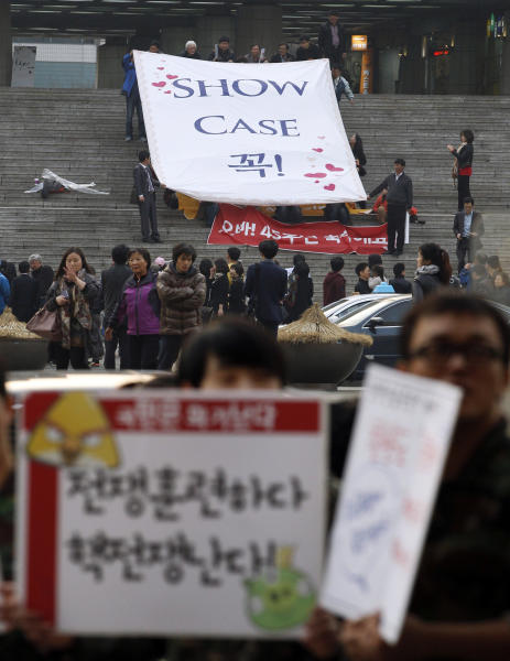 "Fans hold a banner to encourage a singer before the start of his concert as South Korean protesters, bottom, stage a rally denouncing the UN's new sanction against North Korea, and the annual joint military exercises between South Korea and the United Sates, in Seoul, South Korea, Saturday, March 9, 2013. Nearly two decades ago, South Koreans cleared store shelves after a North Korean threat to turn Seoul into a ""sea of fire"" raised war panic. On Saturday, South Koreans expressed some fear but mostly apathy and restraint after a week of warlike rhetoric from the North, including another ""sea of fire"" vow. The letters, bottom left, read "" Stop war exercise."" (AP Photo/Ahn Young-joon)"