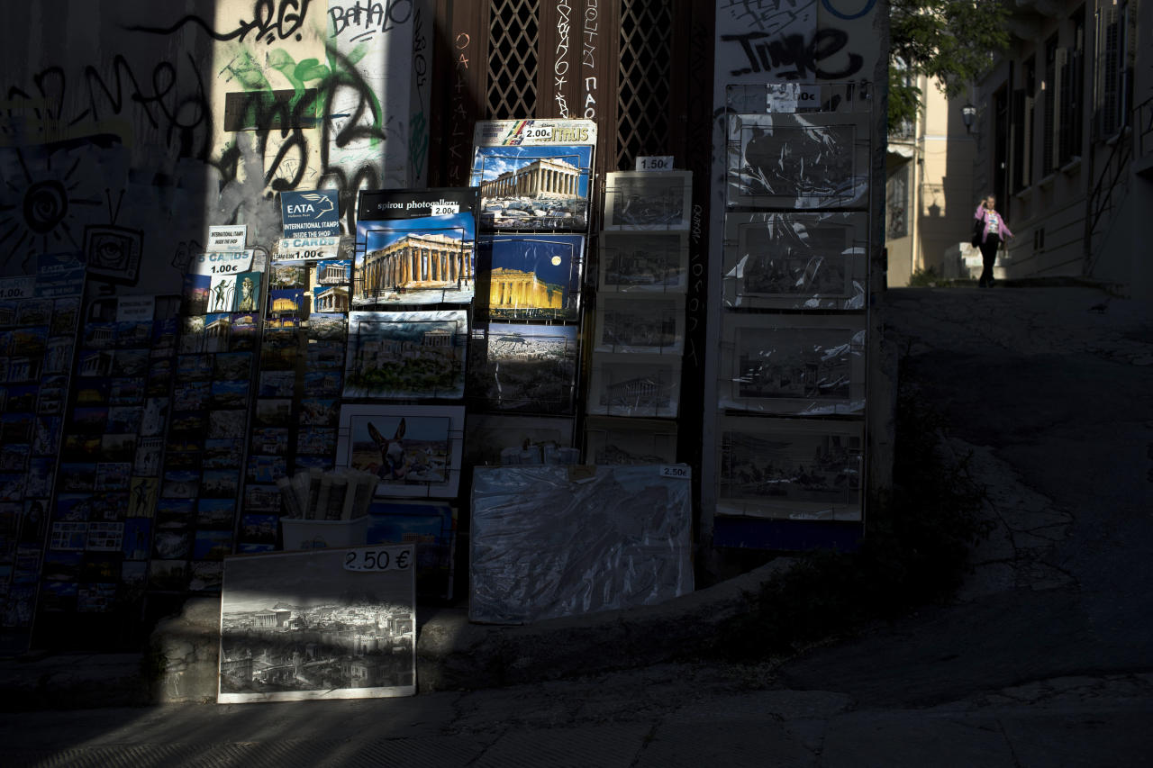 A woman walks past pictures for sale depicting the Ancient Parthenon temple, in Plaka district of Athens, Tuesday, April 24, 2018. Lying under the shadow of the ancient Acropolis Hill, Plaka's narrow streets and neoclassical architecture have for decades attracted tourists and Athenians alike.(AP Photo/Petros Giannakouris)
