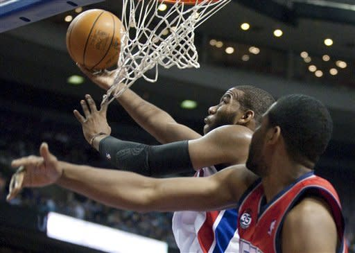 Detroit Pistons' Greg Monroe, left, goes to the basket against New Jersey Nets' Shawne Williams in the second half of an NBA basketball game on Friday, Feb. 10, 2012, in Auburn Hills, Mich. Monroe scored 18 points and pulled down 11 rebounds in the Pistons' 109-92 win.(AP Photo/Duane Burleson)