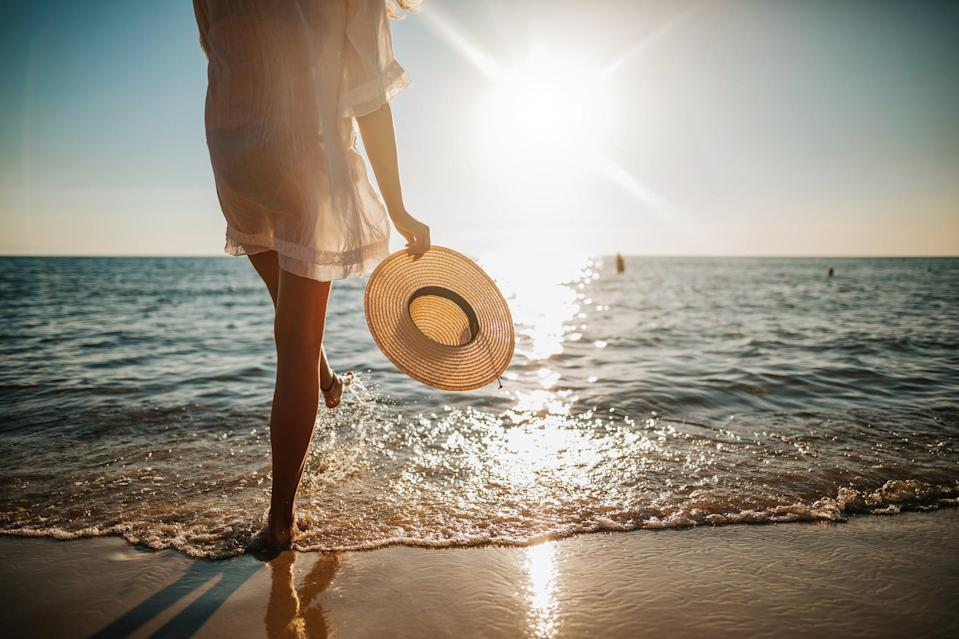 Close-up of young woman in white sun dress and with hat in hand walking alone on sandy beach at summer sunset, splashing water in sea shallow