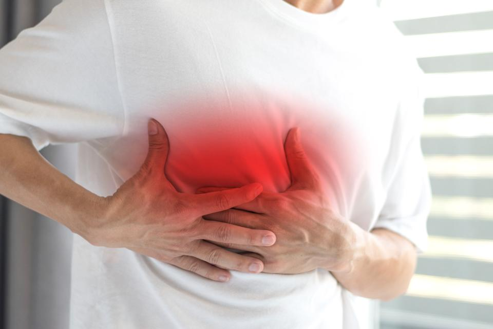 Man's hands on his chest in white shirt with red spot as suffering on chest pain. Male suffer from heart attack,Lung Problems,Myocarditis, heart burn,Pneumonia or lung abscess, pulmonary embolism day