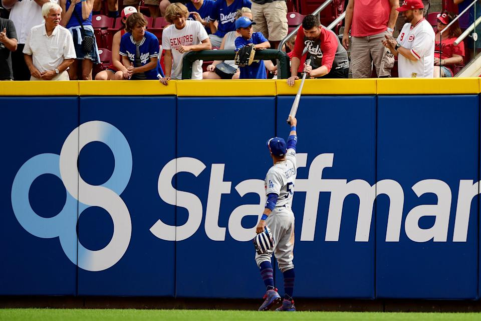 Dodgers outfielder Mookie Betts gives the fan who caught the first major league hit and home run ball by Reds outfielder TJ Friedl a bat in exchange for the ball.