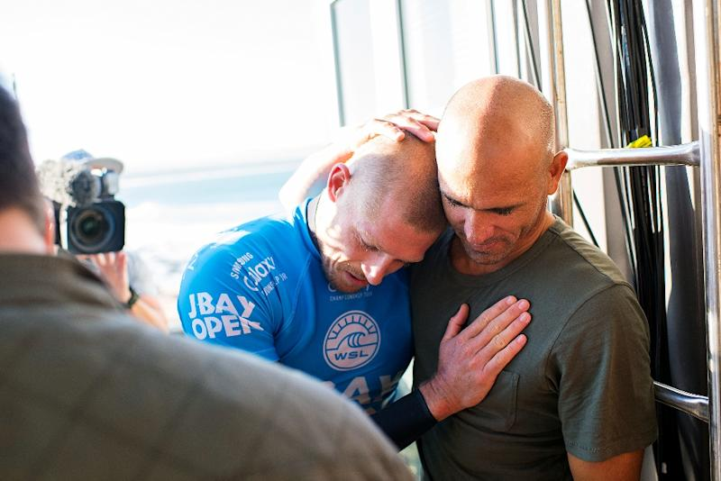 Australian Mick Fanning (pictured blue) is comforted by fellow surfer Kelly Slater of the US after being attacked by a shark during the J-Bay Open final in Jeffreys Bay, South Africa, on July 19, 2015 (AFP Photo/Kirstin Scholtz)