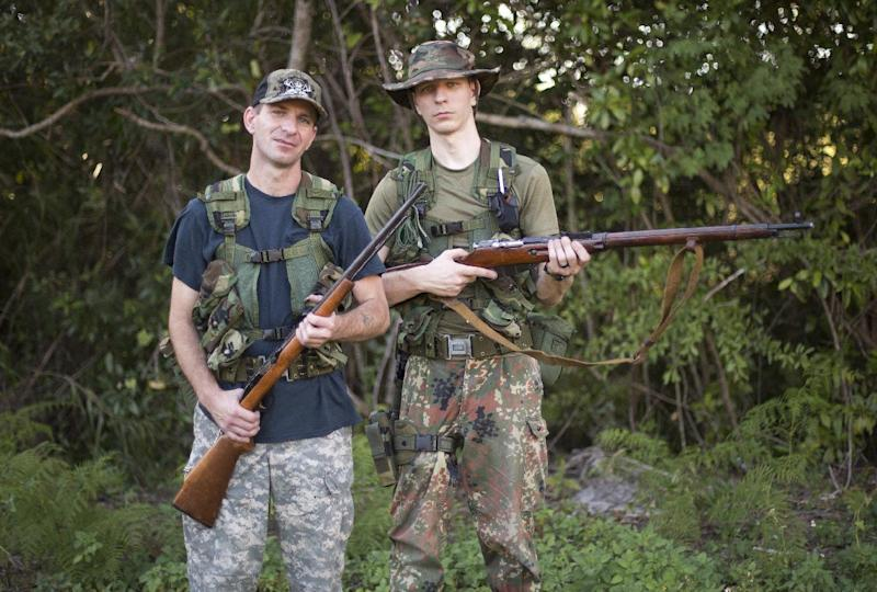 Christopher Padgett, left, and Matthew Manus, from Sebring, Fla. leave their campsite in the Big Cypress National Preserve for their five-day python hunt. The recommended method for killing pythons is a gunshot to the brain, or decapitation to reduce the threat. (AP Photo/J Pat Carter)