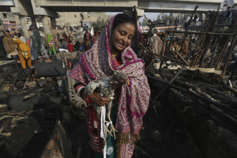 CAPTION CORRECTION: CORRECTS YEAR: A woman holds her chicken that survived a fire in the ruins of gutted homes in Karachi, Pakistan, Wednesday, Jan. 22, 2020. Hundreds of huts were burnt to ashes as fire erupted making dozens of families homeless in a slum of Karachi, local media reported. (AP Photo/Fareed Khan)
