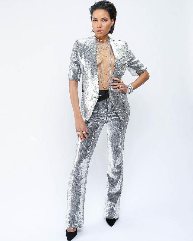 <p>glitters from head-to-toe in a sequin Louis Vuitton suit (sans shirt underneath) and layers of diamond necklaces, earrings and bracelets from Just Desi. </p>