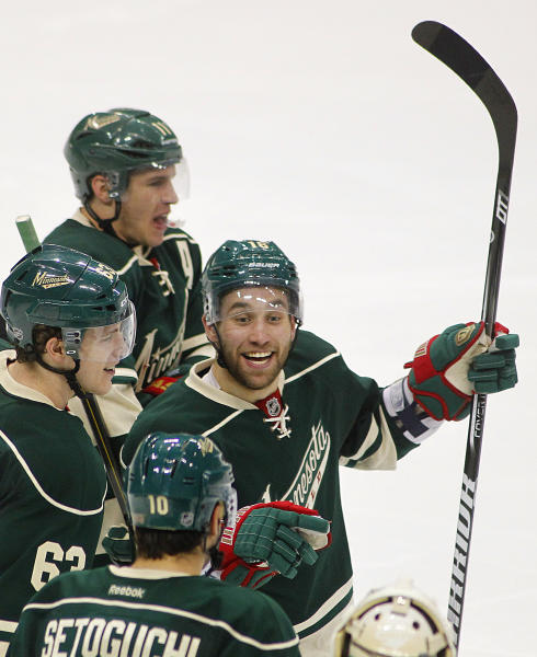Minnesota Wild's Jason Zucker celebrates his overtime goal against the Chicago Blackhawks with teammates Zach Parise, top, Charlie Coyle (63) and Devin Setoguchi during Game 3 of an NHL hockey Stanley Cup playoff series on Sunday, May 5, 2013 in St. Paul, Minn. The Wild defeated the Blackhawks 3-2. (AP Photo/Andy King)