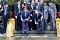 Japanese Prime Minister Yoshihide Suga, center left, and his Vietnamese counterpart Nguyen Xuan Phuc, center right, feed the fish by a pond at the Presidential Palace compound in Hanoi, Vietnam, Monday, Oct. 19, 2020. Suga is on an official visit to Vietnam. (AP Photo/Minh Hoang, Pool)