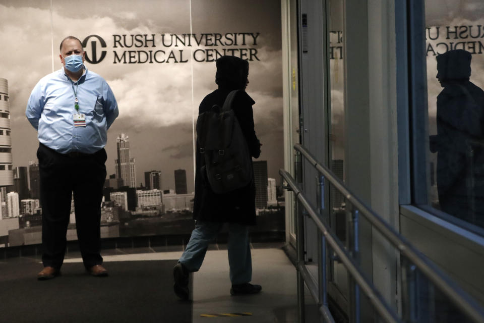 In this Wednesday, April 22, 2020, RUSH Hospital respiratory therapist Jumana Azam accesses a walkway to the hospital before starting her early morning shift in Chicago. (AP Photo/Charles Rex Arbogast)