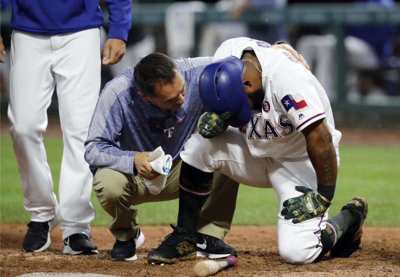 A member of the staff, center, and manager Chris Woodward, left, check on Texas Rangers' Danny Santana, right, who was hit by a pitch from St. Louis Cardinals relief pitcher Carlos Martinez in the ninth inning of a baseball game in Arlington, Texas, Saturday, May 18, 2019. Santana left the game with an unknown injury. (AP Photo/Tony Gutierrez)