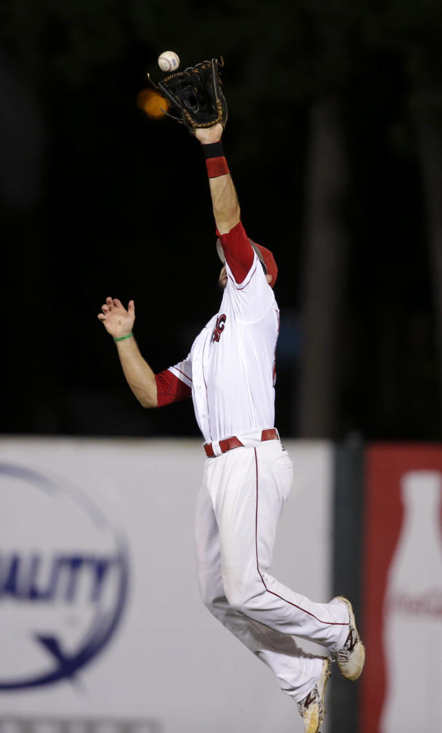 Louisiana Lafayette center fielder Seth Harrison (27) leaps for a bouncing grounder single by Mississippi's Errol Robinson in the second inning of an NCAA college baseball tournament super regional game in Lafayette, La.,Sunday, June 8, 2014. (AP Photo/Gerald Herbert)