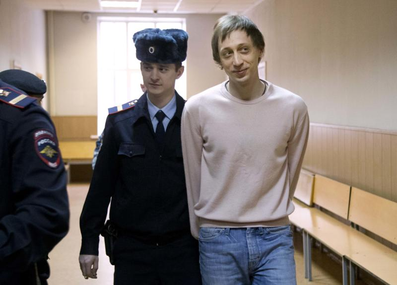 Pavel Dmitrichenko, right, is escorted to a court room in Moscow, Russia, Tuesday, Dec. 3, 2013. Dmitrichenko, a dancer, is on trial for allegedly ordering the Jan. 17 acid attack on the Bolshoi ballet's artistic director Sergei Filin. (AP Photo/Alexander Zemlianichenko)