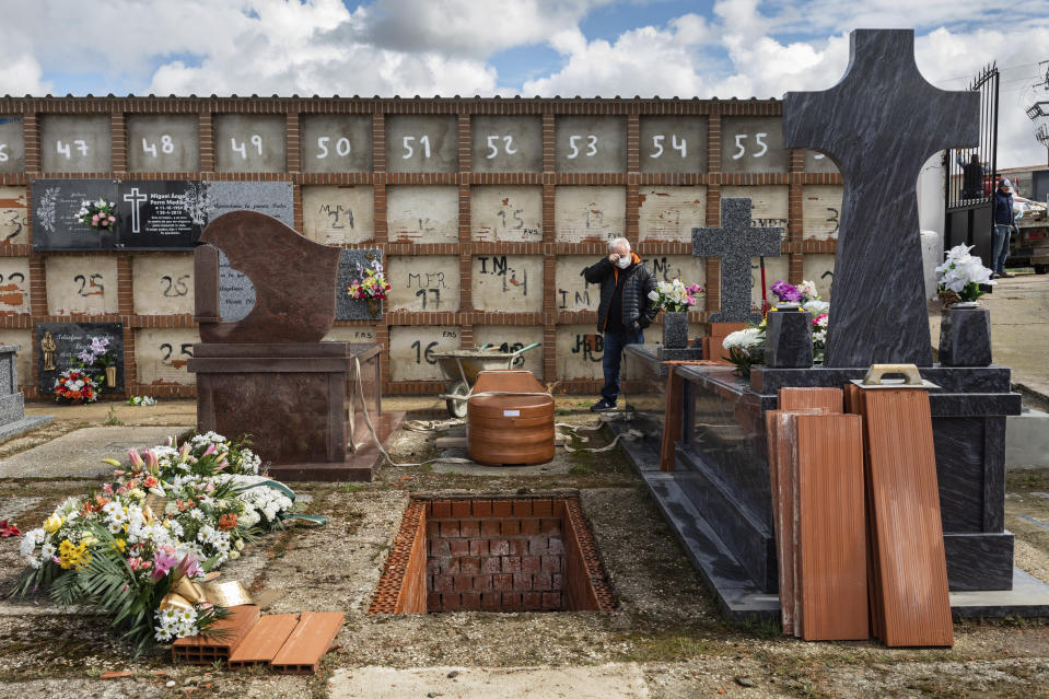 Eusebio Fernandez Cortes, 59, attends the burial of his mother Rosalia Mascaraque, 86, during the coronavirus outbreak in Zarza de Tajo, central Spain, Wednesday, April 1, 2020. Fernandez lost both of his parents within the same week due COVID-19. Intensive care units are particularly crucial in a pandemic in which tens of thousands of patients descend into acute respiratory distress. The new coronavirus causes mild or moderate symptoms for most people, but for some, especially older adults and people with existing health problems, it can cause more severe illness or death. (AP Photo/Bernat Armangue)