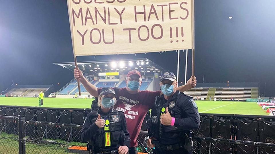 Manly fan Stephen Lucas poses with two police officers, while holding his sign.