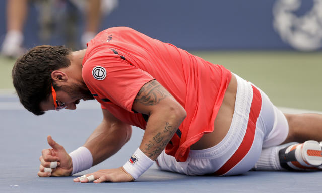 Janko Tipsarevic of Serbia lays on the court after slipping while playing Spain's David Ferrer in the quarterfinals during the 2012 US Open tennis tournament, Thursday, Sept. 6, 2012, in New York. (AP Photo/Peter Morgan)
