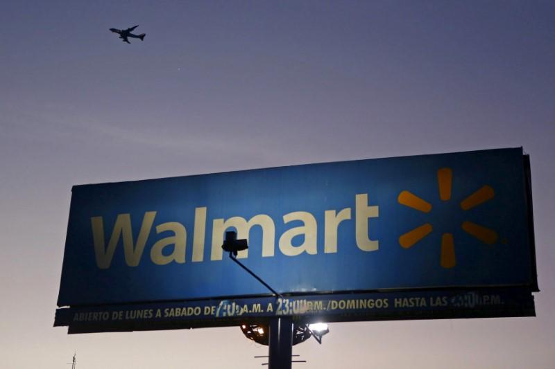 Aircraft flies over a Wal-Mart billboard in Mexico City