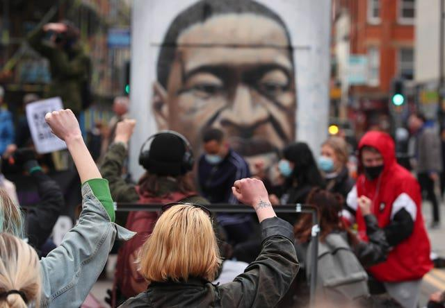 Black Lives Matter demonstrators take a knee in front of a mural of George Floyd in St Peter's Square, Manchester