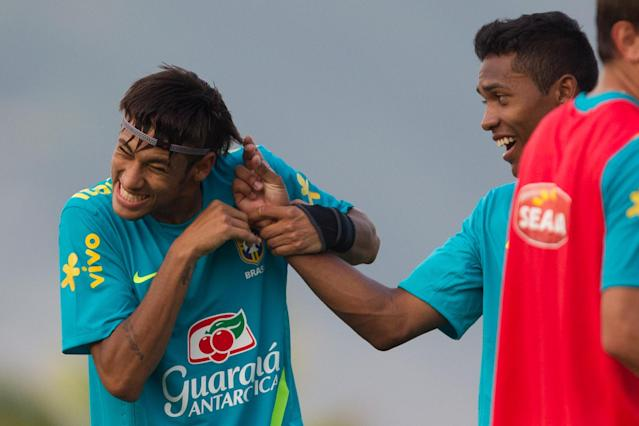 Brazil's Neymar, left, jokes with teammate Alex Sandro during a training session in preparation for the London 2012 Olympics in Rio de Janeiro, Brazil, Wednesday July 11, 2012. (AP Photo/Felipe Dana)