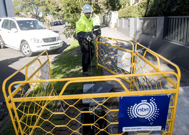 An NBN contractor can be seen laying fibre cable in a ditch in Sydney.
