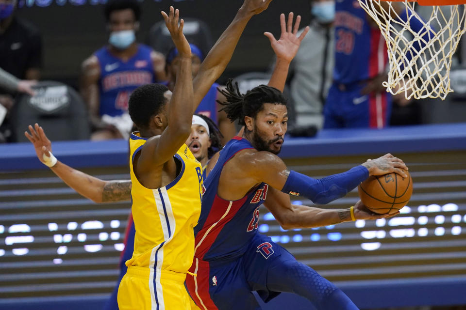 Detroit Pistons guard Derrick Rose, right, passes the ball while defended by Golden State Warriors forward Andrew Wiggins during the first half of an NBA basketball game in San Francisco, Saturday, Jan. 30, 2021. (AP Photo/Jeff Chiu)