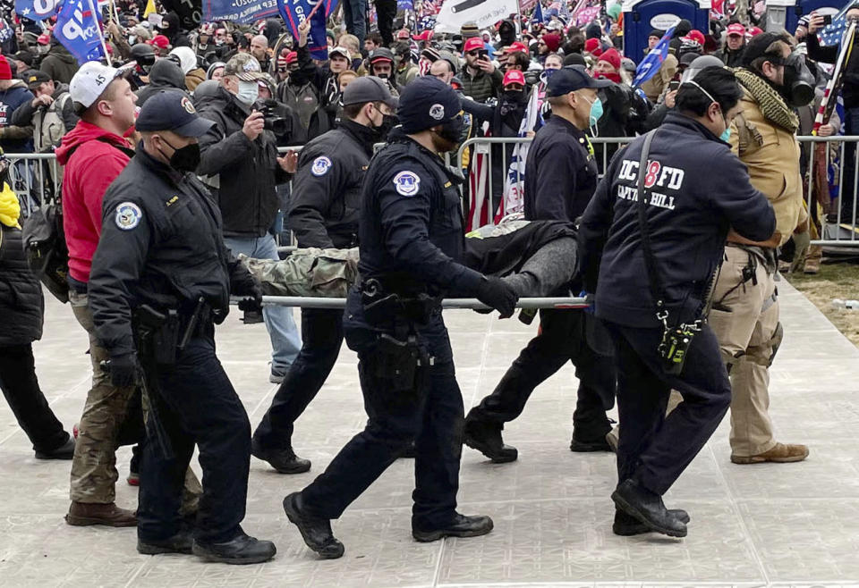 A Capitol Police Officer is carried from the Capitol during the riots. Source: AAP