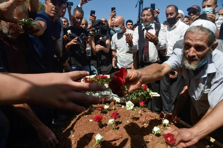 A group of Algerian mourners gathered around Bouteflika's tomb after his muted funeral to decorate it with roses (AFP/Ryad KRAMDI)