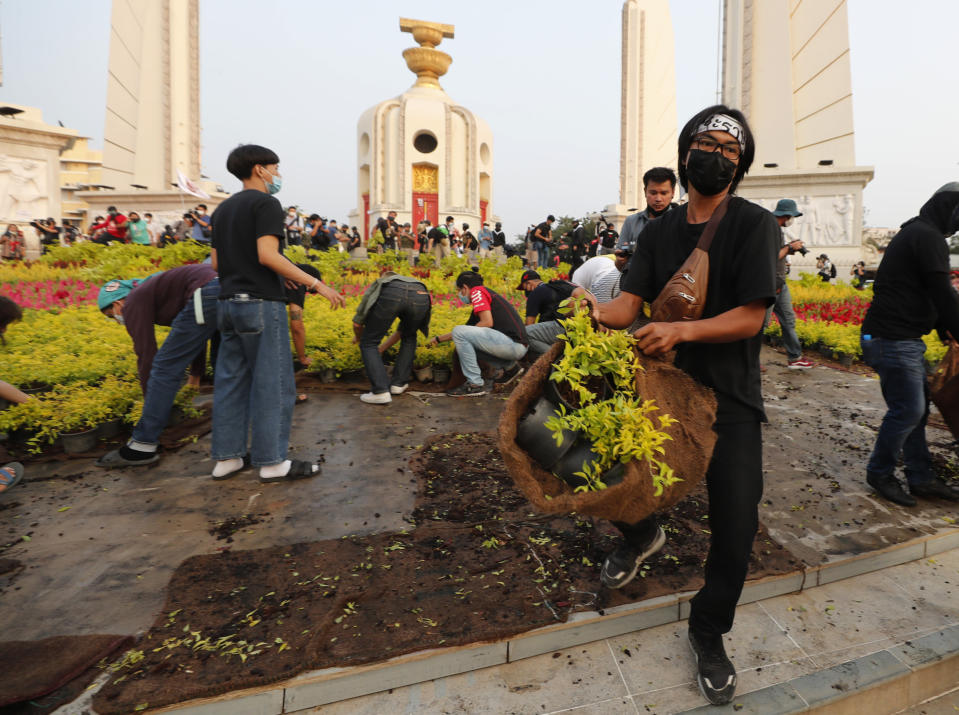Pro-democracy protesters remove flowers and plant pots from around the Democracy Monument during a rally at Democracy Monument in Bangkok, Thailand, Saturday, Feb. 13, 2021. The rally in the Thai capital was organized by the Ratsadorn movement, which campaigned last year for Prime Minister Prayuth Chan-ocha and his government to step down, the constitution to be amended and the reform of the monarchy to make it more accountable. (AP Photo/Sakchai Lalit)