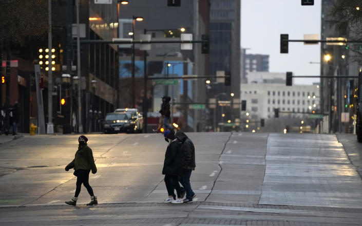 Pedestrians wear masks while crossing an empty road at the intersection of Market Street and 15th Avenue during the evening rush hour Monday, Dec. 28, 2020, in downtown Denver. (AP Photo/David Zalubowski)