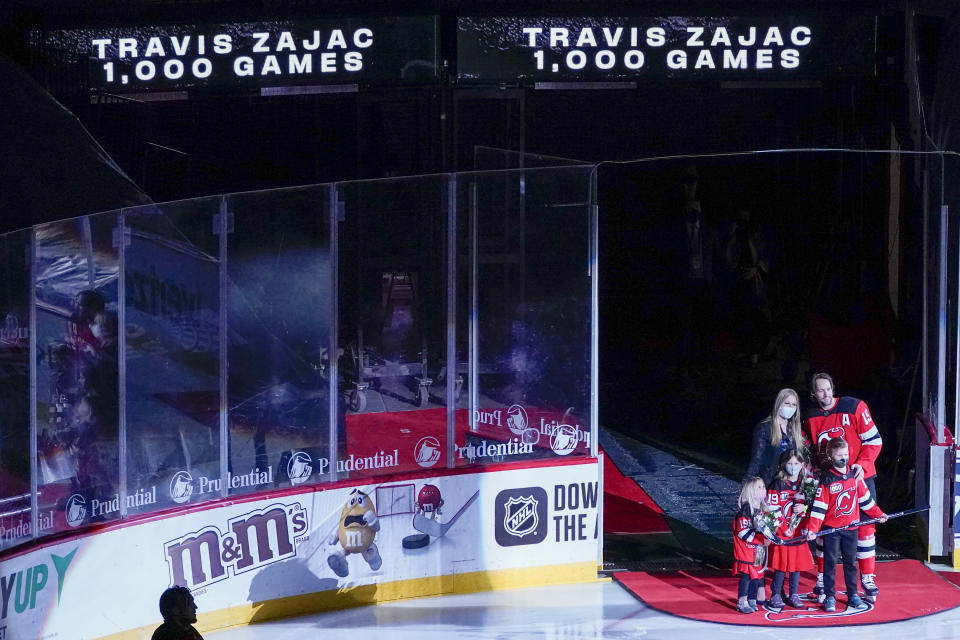 New Jersey Devils center Travis Zajac is joined by his family during a ceremony to celebrate his 1,000 career games with the New Jersey Devils before he start of an NHL hockey game against the Washington Capitals, Saturday, Feb. 27, 2021, in Newark, N.J. (AP Photo/Mary Altaffer)