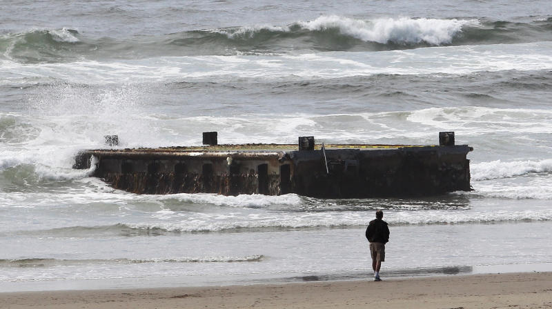 <p>               FILE -In this file photo from Wednesday, June 6, 2012, a man looks at a 70-foot-long dock with Japanese lettering that washed ashore on Agate Beach in Newport, Ore. The West Coast is anticipating more debris from the 2011 Japanese tsunami to wash ashore this winter. Scientists expect the bulk of the tsunami debris to end up in the Pacific Northwest. (AP Photo/Rick Bowmer, File)