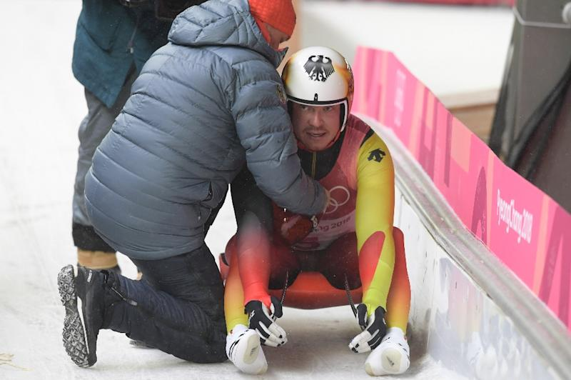 Germany's Felix Loch is consoled by his coach after a late error in the Olympic men's luge